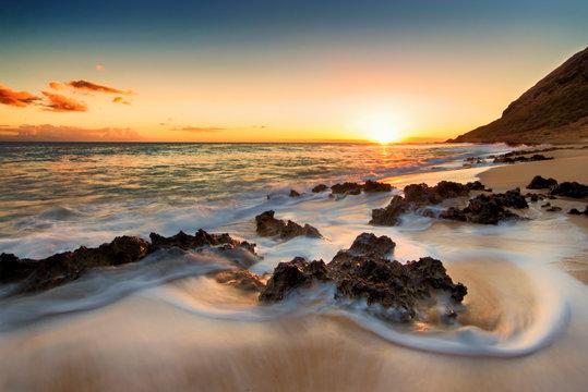 Slow exposure of waves washing around lava rocks on beach on west side of Oahu, Hawaii