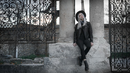 Fashion girl in a hat with white hair, in black clothes, sits near the gate of the castle.