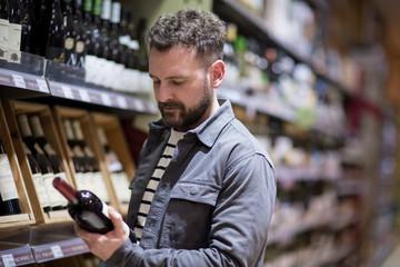 Man choosing wine in grocery store
