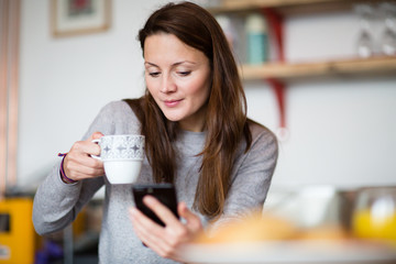 Young adult female having morning coffee and checking smartphone
