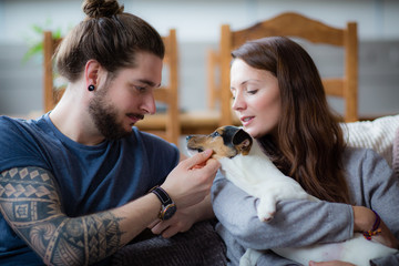Young couple with pet puppy Jack Russell