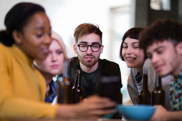 Group of friends looking at a smartphone together in a pub