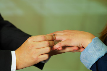 Close up shot of man putting ring on his girlfriend hand