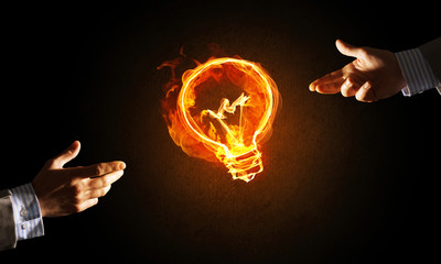 Concept of electricity or inspiration with burning light bulb and creation gesture