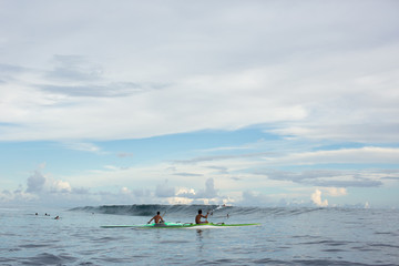 Kayakers and surfers on sea, Tahiti, South Pacific