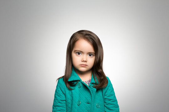 Portrait of girl standing against gray background