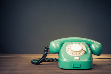 Retro mint green rotary telephone on wood table