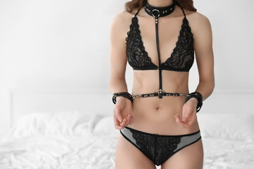 Young beautiful woman with bdsm accessory near bed