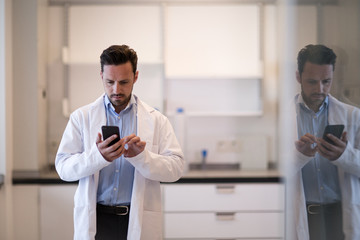 Male scientist using smartphone in laboratory