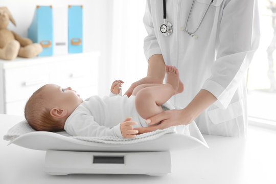 Female doctor weighting cute baby in clinic