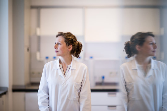 Female scientist looking out of window with reflection