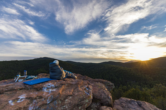woman in a sleeping bag looking out at the mountains