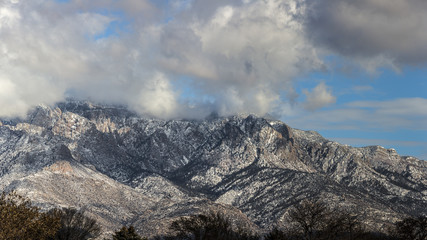 low clouds surrounding a mountain lightly covered in snow