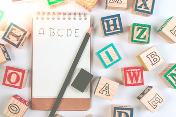 Wood letter blocks alphabet ABC with notebook worksheet for practice alphabet handwriting drill.