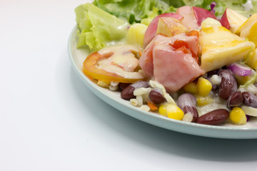 Closeup mixed of fresh salad and fruit on dish. Corn, red beans, pineapple and papaya on white background.