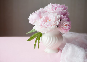 Light pink double Peonies in white ceramic vase, lace and copy space.
