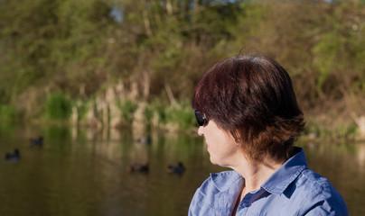 Older Lady Sitting Beside Lagoon Looking at Ducks