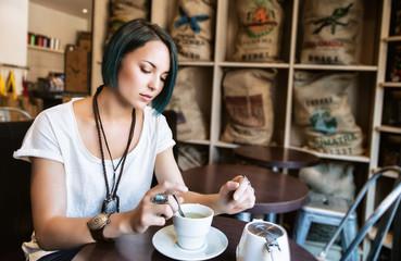 Jeune femme devant sa tasse de thé dans un bar