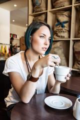 Jeune femme boit une tasse de thé dans un bar
