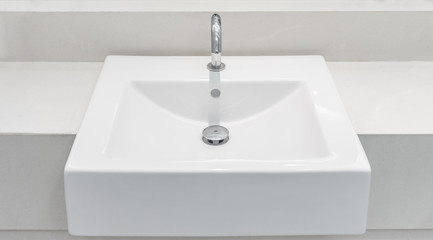 White ceramic wash basin with a automatic tap and drain. It is also known as sink, sinker, washbowl and hand basin. Fototapete
