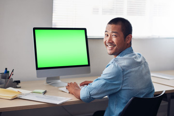 Smiling young Asian designer at work on an office computer