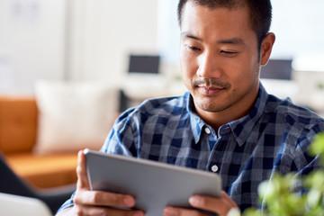 Focused Asian designer using a tablet in a modern office Fotoväggar