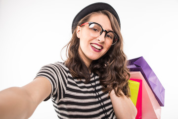 Beautiful smile girl wearing hat and glasses holding shopping bags and taking selfie with cell phone isolated on white background