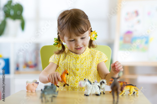 Happy little girl. Smiling child toddler plays animal toys at home or kindergarten.