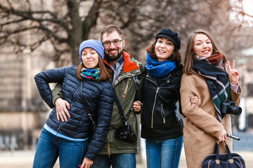 A team of four happy friends students hugs and laughs in the park of a European city in the winter, travel concept