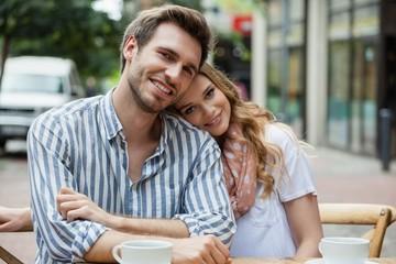 Portrait of romantic couple sitting at sidewalk cafe