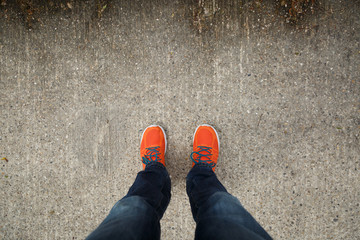 Man with orange shoes standing on a textured, concrete city street.