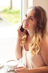 A beautiful young woman sitting in a café. Girl talking on the phone. Girl drinks Cappuccino.