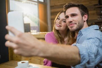 Young couple taking selfie on mobile phone while having coffee