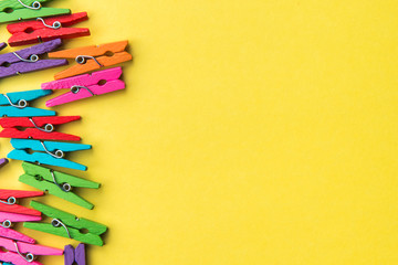 Colorful laundry clips on yellow background.