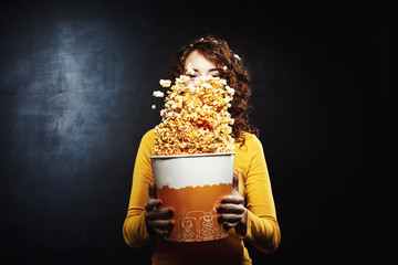 Pretty girl having fun at movie theatre shaking popcorn bucket