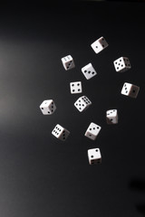 Dice fall over a set of cards on black background. Throwing dice on black background