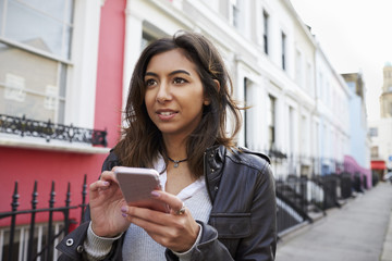 Young woman using mobile phone in residential city street