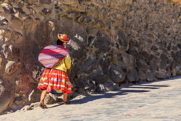 Peruvian woman cholita dressed in traditional colorful cloth, carrying the sack and walking up the street with stony walls, Inkan Sacred Valley, Ollantaytambo, Peru