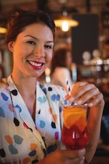 Portrait of young woman having cocktail drink