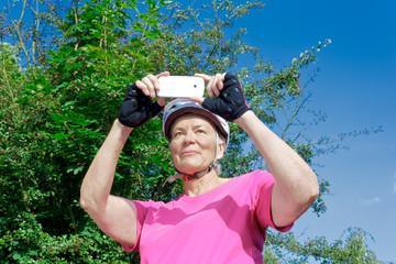 senior cyclist taking photo phone
