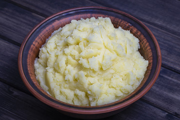 Mashed potatoes in a plate on the wooden table