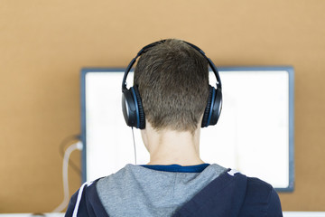 A young man behind a computer screen with headphones on, seen from the back.