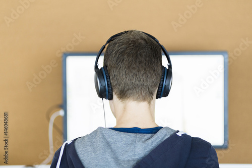 a young man behind a computer screen with headphones on seen from