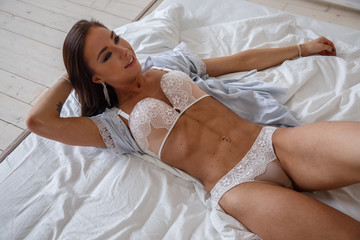 Beautiful girl sexy fitness underwear poses in a bright room in the morning