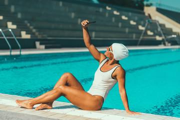 Female swimmer making selfie on poolside