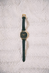 flat lay of an elegant black and golden wristwatch on white background. top view.