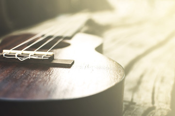 close-up ukulele on wood background. over light vintage style.