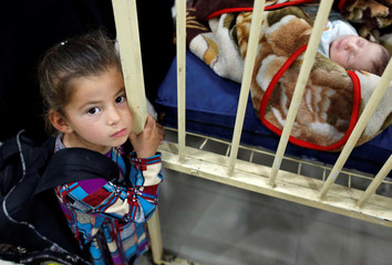 An Iraqi girl stands next to her brother's bed at a children's hospital, in eastern Mosul