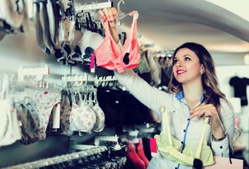 Woman client choosing bra in underwear store