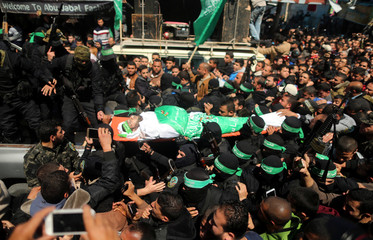 Palestinian members of Hamas' armed wing carry the body of senior militant Mazen Fuqaha during his funeral in Gaza City